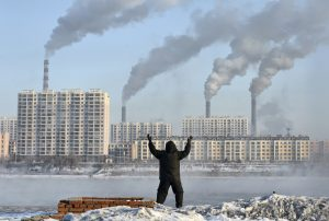 An elderly man exercises in the morning as he faces chimneys emitting smoke behind buildings across the Songhua river in Jilin, Jilin province, February 24, 2013. China's new rulers will focus on consumer-led growth to narrow the gap between rich and poor while taking steps to curb pollution and graft, the government said on Tuesday, tackling the main triggers for social unrest in the giant nation. Picture taken February 24, 2013. REUTERS/Stringer (CHINA - Tags: ENVIRONMENT BUSINESS POLITICS) CHINA OUT. NO COMMERCIAL OR EDITORIAL SALES IN CHINA - RTR3EL55